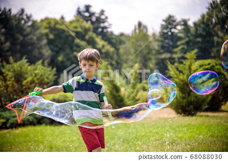 Little boy playing with his soap bubbles toy in 68088030