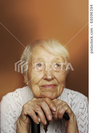Senior Woman Relaxing In Chair Holding Walking 68096394