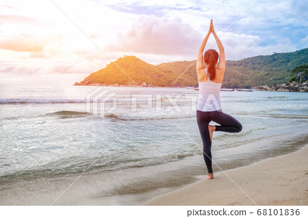 Young beautiful woman practicing yoga on the beach 68101836