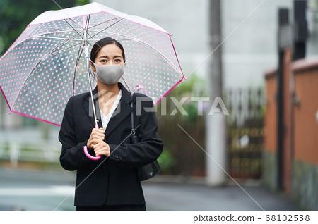 通勤的婦女與在雨中戴著面具的乙烯基傘一起工作 68102538