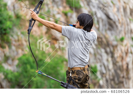 Man wearing cargo pants and holding archer 68106526