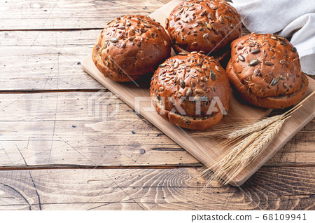 Bread products with cereals and seeds on a wooden background. Lean healthy buns, carbohydrate pastries. Copy space 68109941
