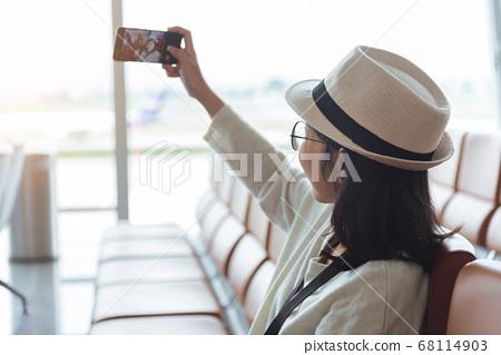 Smiling young Asian woman traveler taking selfie 68114903