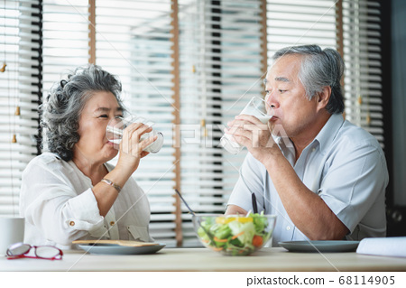 Smiling Asian senior man and woman drinking glasses of milk 68114905