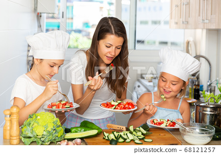 Little cooks learn with their mom how to cook a salad in the kitchen 68121257