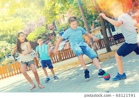 Happy children playfully running after ball outdoors in park 68121591