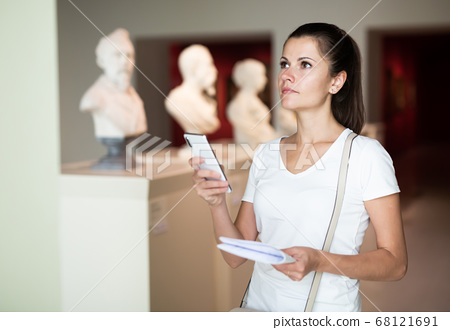 Woman using phone searching information about sculptures 68121691