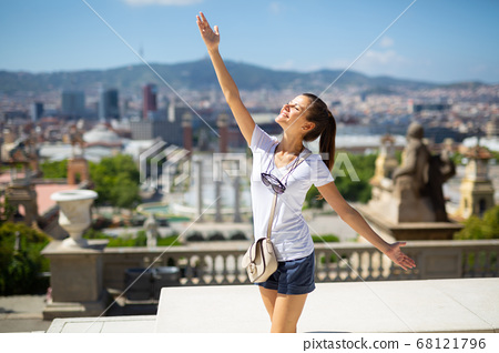 Woman with arms up enjoying sunny day 68121796