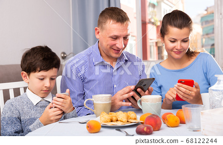 Boy and his parents using phones 68122244