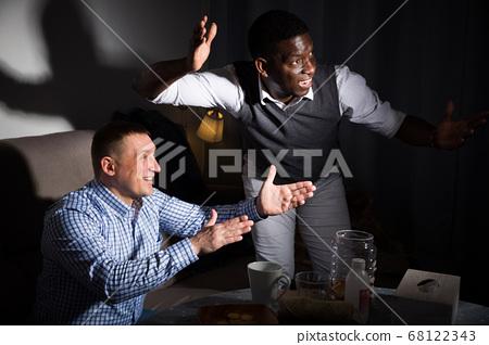 Positive male interracial friends watching football match on tv 68122343