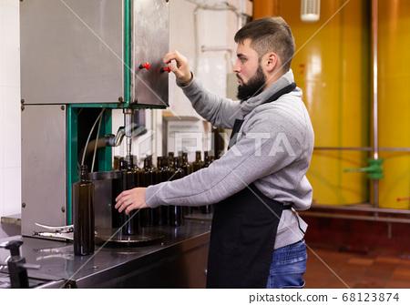 Guy working on olive oil bottling conveyor 68123874