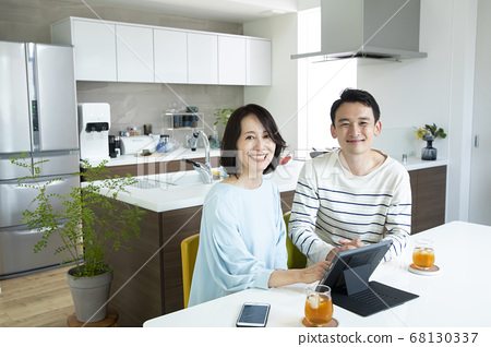 父母和孩子一起看個人計算機的一個年輕人和一個中間婦女 68130337