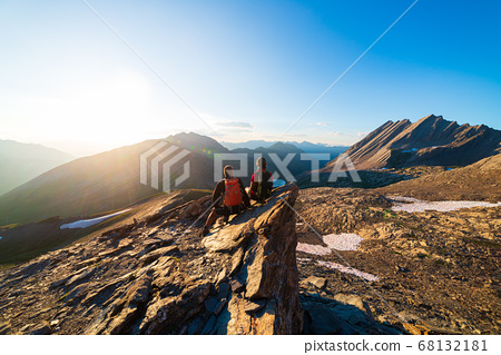 Couple of hikers looking at view from mountain top 68132181