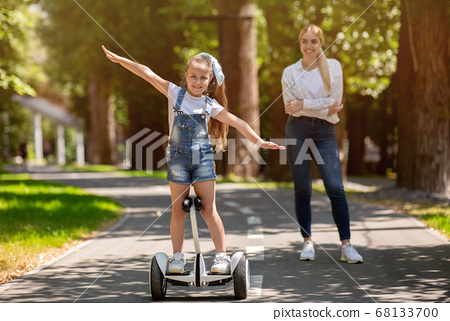 Little Girl Riding Segway Spending Weekend With Mother In Park 68133700