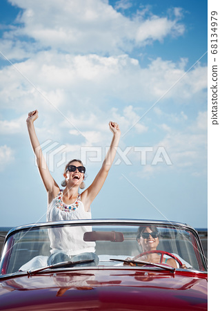 Happy Women Driving Rented Convertible Car For Vacations 68134979