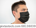 Black protective mask on the young guy's face, portrait 68136039