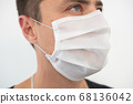 White protective mask on the young guy's face, portrait 68136042