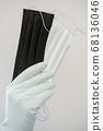 Man holds rubber gloves black and white face masks 68136046
