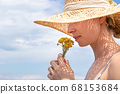 Portrait of young beautiful cheerful woman wearing straw sun hat, smelling small bouquet of yellow wild florets, against blue summer sky 68153684