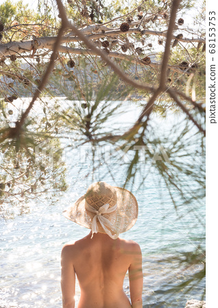 Rear view of topless beautiful woman wearing nothing but straw sun hat realaxing on wild coast of Adriatic sea on a beach in shade of pine tree. 68153753