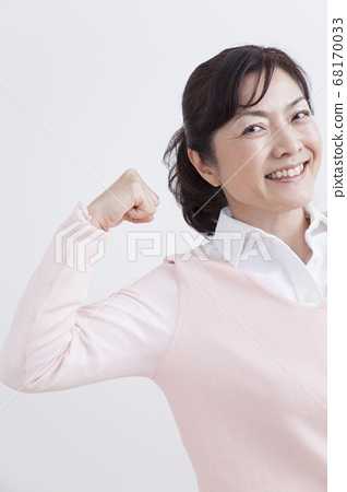 A middle woman who makes a guts pose 68170033