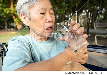 Asian senior woman holding glass of water,hands shaking while drinking water,elderly with hands tremor uncontrolled body tremors,symptom of essential tremor,parkinson's disease,neurological disorders 68183812