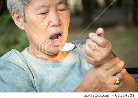 Asian senior woman holding spoon and hands tremor while eating rice,cause of hands shaking include parkinson's disease,stroke, brain injury,symptom of essential tremor,health problem of elderly people 68184301