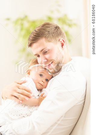 Father cuddles his daughter in his arms, both 68186040