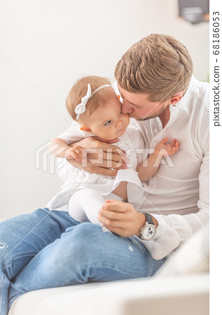 Young father holding and kissing his baby toddler 68186053