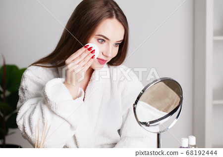 Smiling young woman washing her face with facial cleansing sponge at bathroom 68192444
