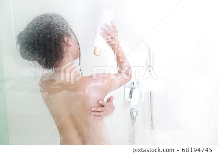 back view blurred image through glass of young sexy asian woman who is showering in bathtub 68194745