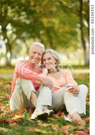 Senior couple sitting on autumn leaves in park 68199343