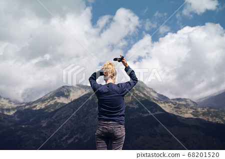 rear view of woman arranging her hair in front of 68201520