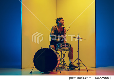 Young caucasian musician inspired performing on yellow background in neon light 68229001