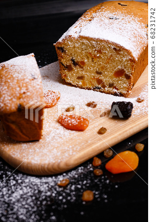 Sweet cupcake in the shape of bread. Cupcake with raisins, dried apricots, plums. 68231742