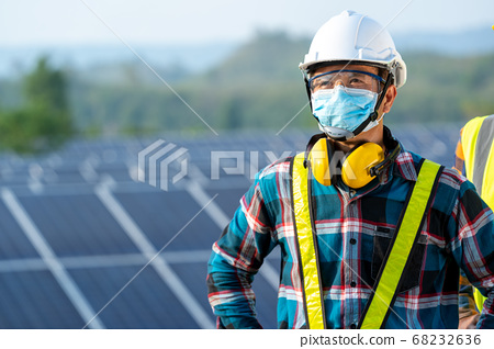 Electrician with engineer wearing a medicine healthcare mask working and checking at solar power station 68232636