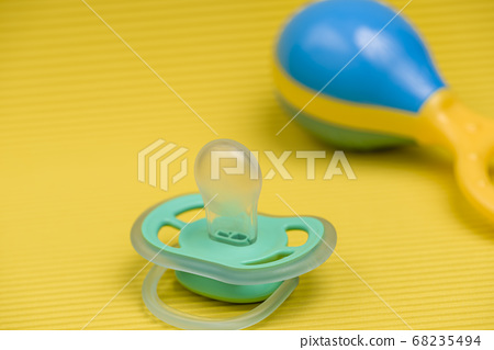 Baby Pacifier on a yellow background with a 68235494