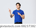 Carefree smiling asian guy in blue t-shirt, gazing at upper left corner, pointing fingers at promo or banner. Man on self-quarantine during covid-19 look out window, standing grey background 68237382