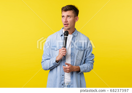 Lifestyle, people emotions and summer leisure concept. Handsome blond man in casual clothes perform in fron audience, holding microphone and looking away thoughtful, give speech on stage 68237397