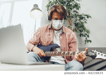 Young man plays guitar at home in medical mask. Coronavirus quarantine lifestyle concept 68238635