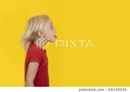 Blond boy in red shirt shows tongue. Portrait side 68248046