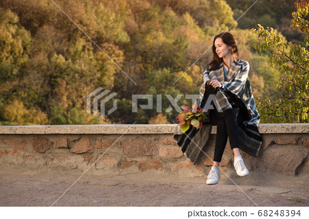 Pretty girl sit on the roadside on the background 68248394