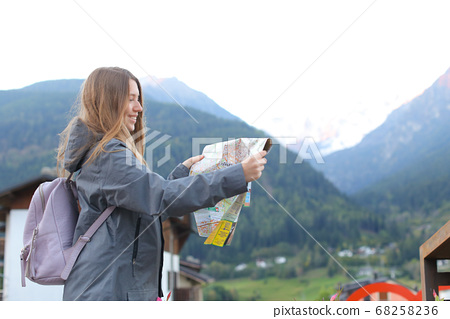 Back view caucasian girl looking at map in mountain village. 68258236