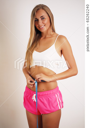 Young athletic slender woman measures the waist. The girl measures the waist with a centimeter tape. 68262240