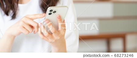 在客廳裡操作智能手機的年輕女子。 68273246