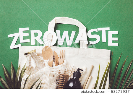 Zero waste concept. Cotton bag, bamboo cultery, glass jar, bamboo toothbrushes, hairbrush and straws on green background 68275937