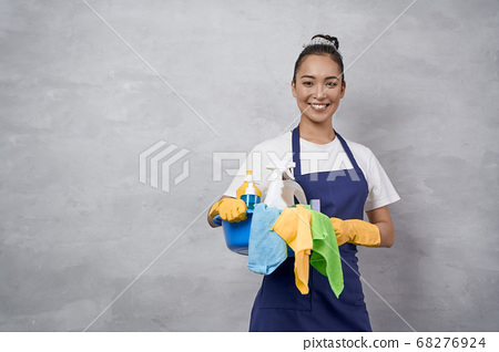 Young happy woman, female cleaner in uniform and rubber gloves holding bucket of cleaning supplies and smiling at camera, standing against grey wall 68276924