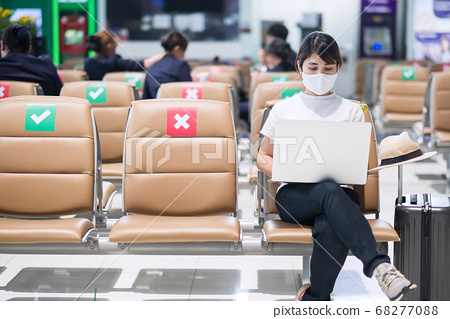 Young female wearing face mask and using computer 68277088