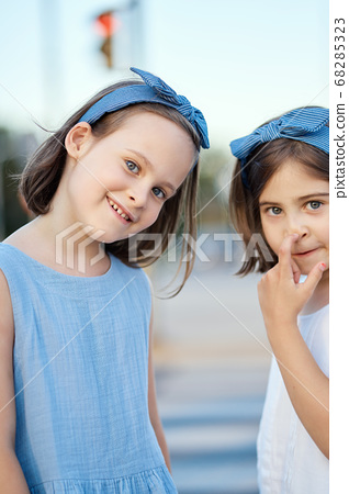 two cute little girls are walking along the city streets at sunset 68285323