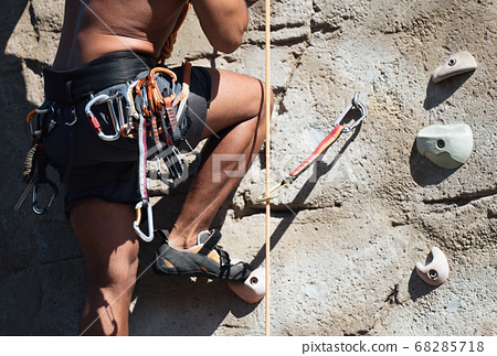 Sportsman climber moving up on steep rock, climbing on artificial wall outdoors. Extreme sports and bouldering concept 68285718